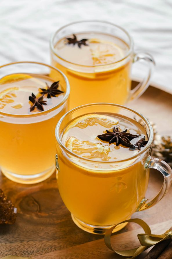 close up of mulled white wine in glasses on wood plate