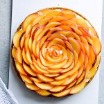 Whipped mascarpone peach tart - crumbly cookie crust filled with vanilla whipped mascarpone and topped with fresh peaches shaped like a rose! A truly impressive dessert. | sugarsalted.com