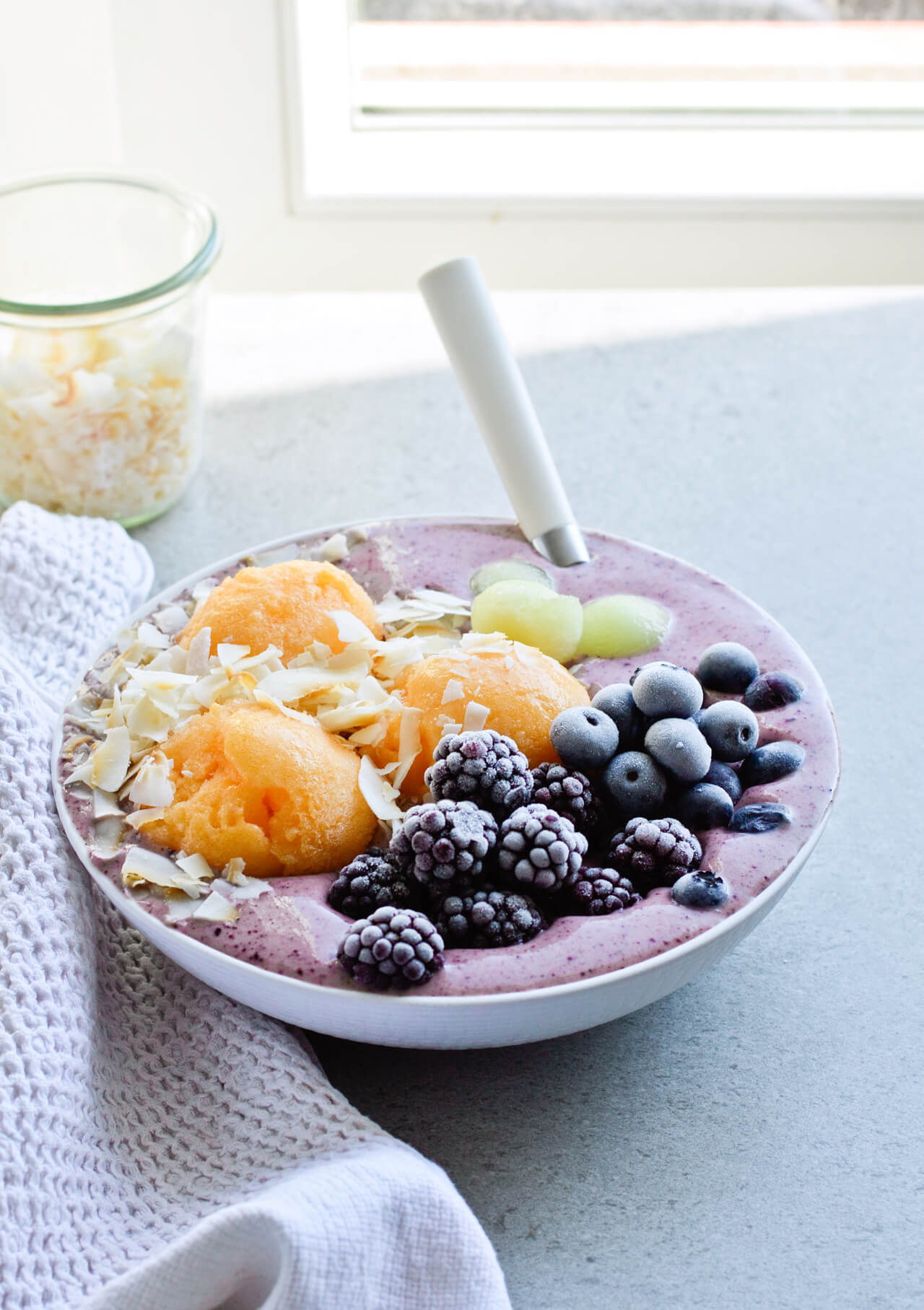Berry banana frozen smoothie bowl, made with vanilla yogurt, acai powder and a lot of fruit! Topped with some peach sorbet and coconut chips for extra flavor. A great, healthy breakfast or even lunch. | sugarsalted.com