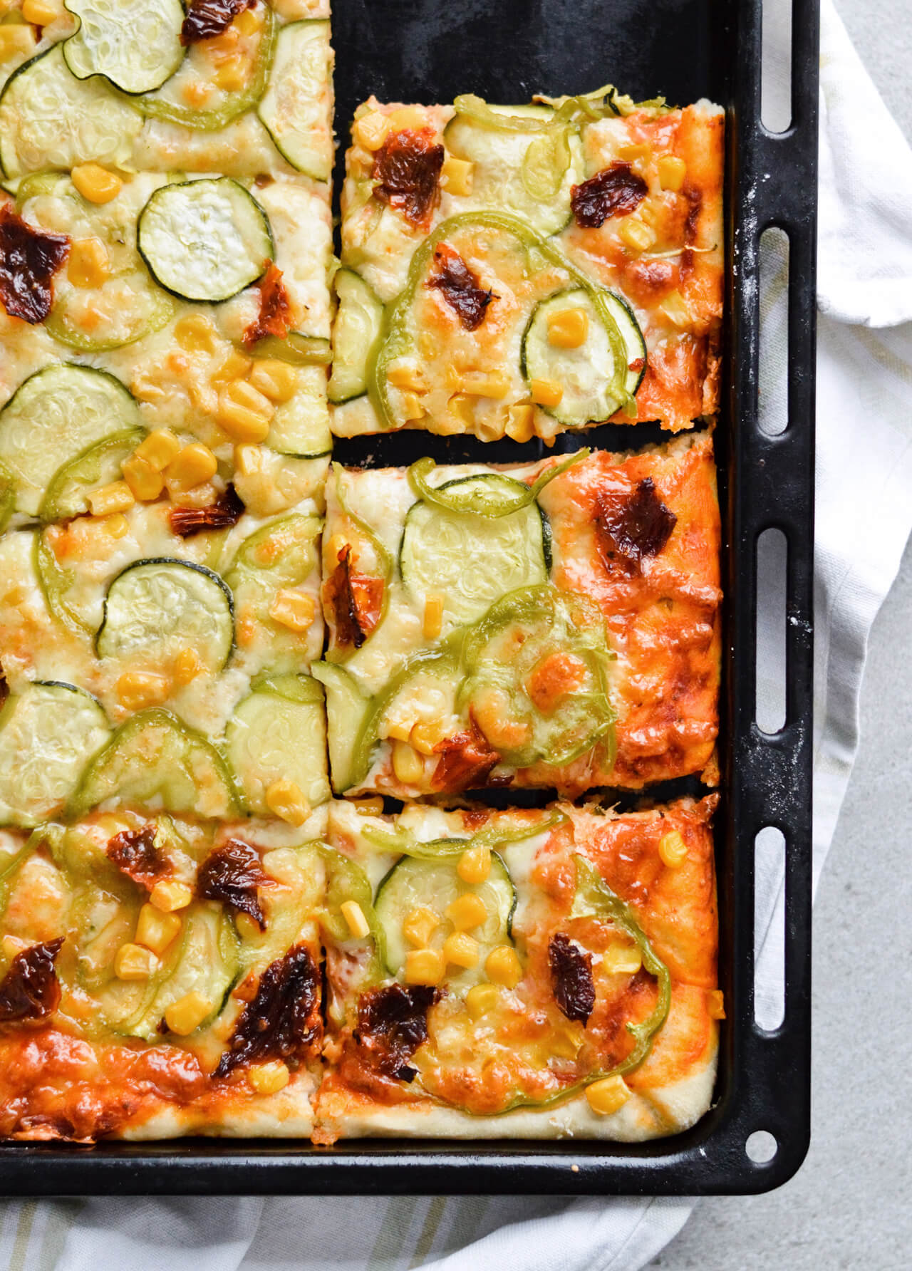 Best vegetable sheet pizza! Made with homemade pizza dough and quick pizza sauce, topped with zucchini, peppers, corn and much more! So easy to make, great for dinner and a crowd. | sugarsalted.com