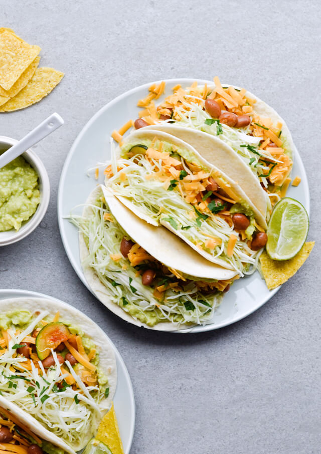 Guacamole cabbage bean tacos are the best vegetarian tacos! With easy homemade guacamole, zesty cabbage, zucchini, paprika beans and lots of cheddar! | sugarsalted.com