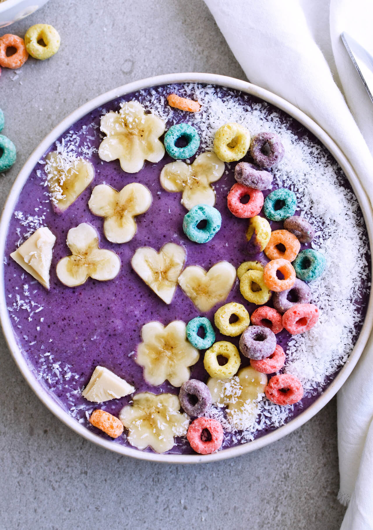Recipe for creamy, nourishing Coconut blueberry oat smoothie. Made with oats, chia seeds, almond butter and more - this truly is the perfect breakfast! Topped with coconut and pretty froot loops! | sugarsalted.com