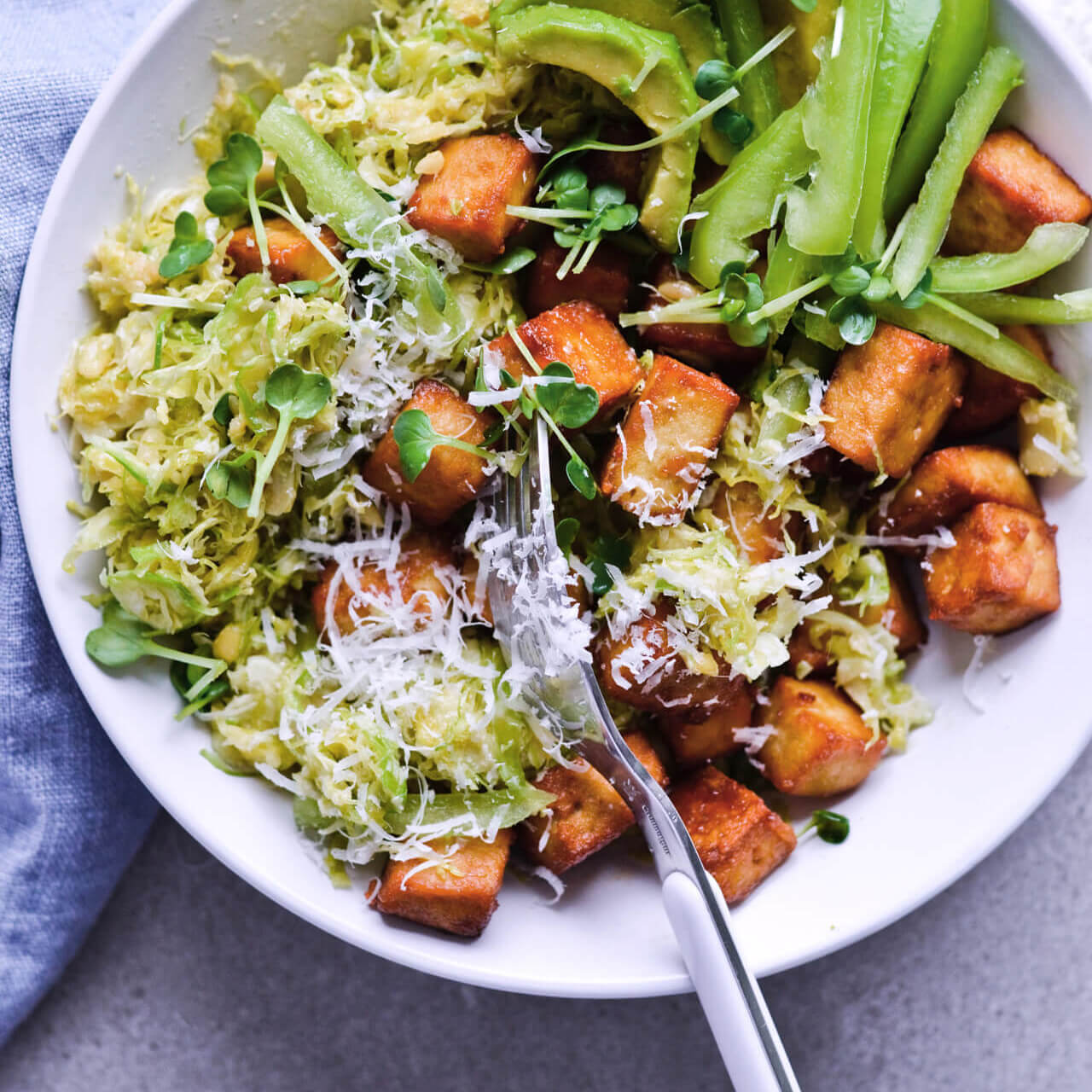 Recipe for Crispy tofu shaved brussels sprout salad with honey mustard dressing, pine nuts and Parmesan. Easy to make, very filling and vegetarian meal. | sugarsalted.com