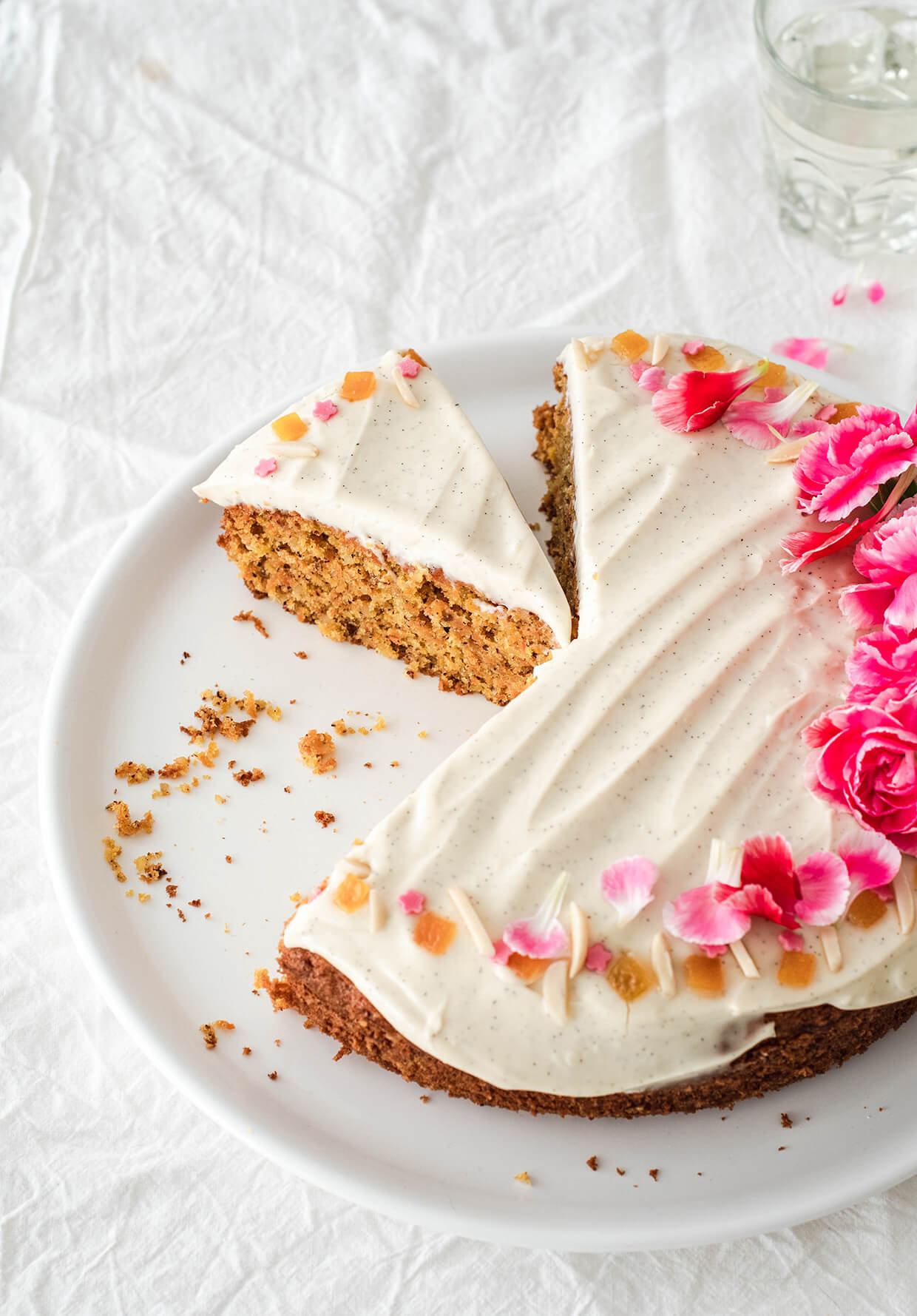 Recipe for Orange almond carrot cake with creme fraiche frosting - sliced cake on plate with flowers