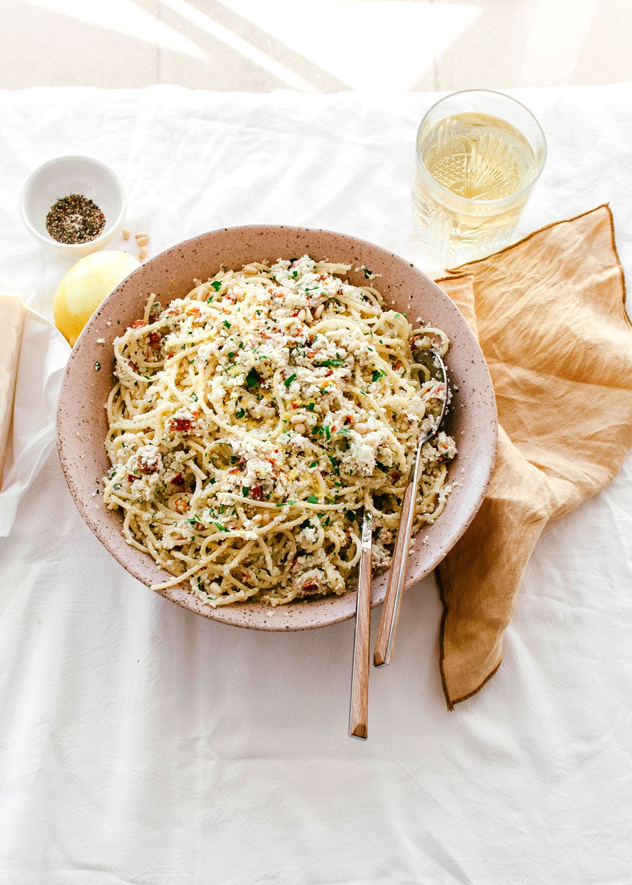 sunlit table with large bowl serving of spaghetti with cauliflower pesto, cheese, pepper, lemon and glass of wine
